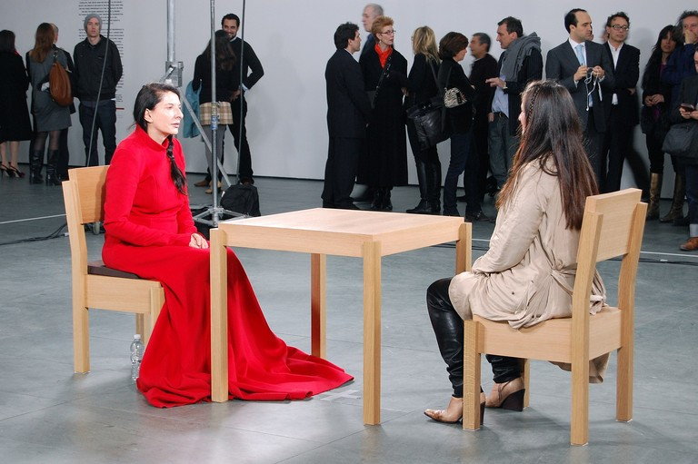 Marina Abramović, The Artist is Present, 2010, Museum of Modern Art, New York, 9 March – 31 May 2010. Image courtesey of Andrew Russeth [CC BY-SA 2.0 (https://creativecommons.org/licenses/by-sa/2.0)], via Wikimedia Commons.